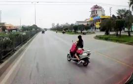 Video: Cô gái vừa cởi áo mưa, vừa ôm em bé chạy xe